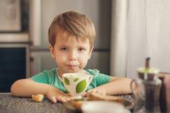 El muchacho alegre bebe la leche, come la tostada para el desayuno Imagen de archivo libre de regalías