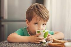 El muchacho alegre bebe la leche, come la tostada para el desayuno Imagenes de archivo