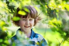 El muchacho alegre con risas del pelo rizado y pieles en ramas de árbol foto de archivo