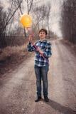 El muchacho alegre con un globo Fotos de archivo