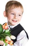 El muchacho alegre da tulipanes hermosos Imágenes de archivo libres de regalías