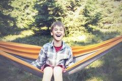 El muchacho alegre está balanceando en una hamaca y una risa Foto de archivo libre de regalías