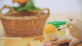 El muchacho alegre está pintando un huevo de Pascua en un color amarillo con una ayuda de la brocha