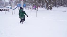 El muchacho alegre hermoso del preescolar corre lejos a través de las nieves acumulada por la ventisca profundas almacen de metraje de vídeo