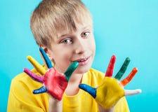El muchacho alegre hermoso en la demostración amarilla de la camiseta pintó las manos Fotografía de archivo