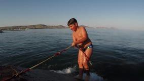 El muchacho alegre sale de la agua de mar al embarcadero metrajes