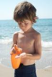 El muchacho aplica la protección solar en su mano Imagen de archivo