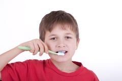El muchacho aplica los dientes con brocha Fotografía de archivo