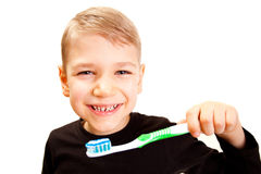 El muchacho aplica los dientes con brocha Imagen de archivo libre de regalías