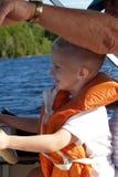 El muchacho aprende conducir el barco Imagen de archivo