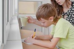 El muchacho aprende escribir las letras que se sientan por la tabla Hacer la preparación con su mamá imagen de archivo