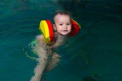 El muchacho aprende permanecer en el agua foto de archivo
