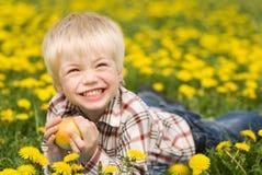 El muchacho arranca con los dientes una manzana Foto de archivo libre de regalías