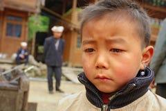 El muchacho asiático 8 años, está llorando en calle del pueblo. Foto de archivo libre de regalías