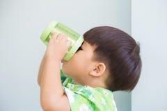 El muchacho asiático de Thristy que bebe cerca soporta la taza Fotografía de archivo