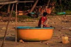 El muchacho asiático en camiseta roja se sienta en barco anaranjado redondo Fotografía de archivo libre de regalías