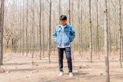El muchacho asiático en la chaqueta casual y de los vaqueros blanca se está colocando en el Dr. Fotos de archivo libres de regalías
