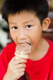 El muchacho asiático goza de su helado del chocolate Foto de archivo