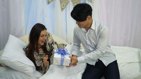 El muchacho asiático hace una sorpresa para su novia el día del ` s de la tarjeta del día de San Valentín mientras que ella duerm metrajes