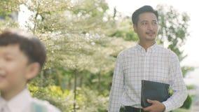 El muchacho asiático que caminaba a través de jardín a la escuela con el padre detrás se encendió en la cámara lenta almacen de video