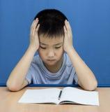 El muchacho asiático serio leyó un libro Imagen de archivo libre de regalías