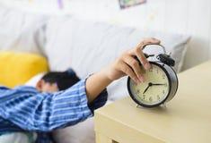 El muchacho asiático soñoliento y apaga caídas del despertador de la cama fotos de archivo libres de regalías