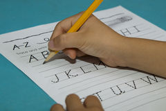El muchacho asiático escribe la letra A con el lápiz amarillo Foto de archivo