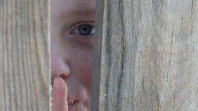 El muchacho asustado del adolescente mira a escondidas con un hueco entre una cerca o una entrada y muestra un finger de una mues metrajes
