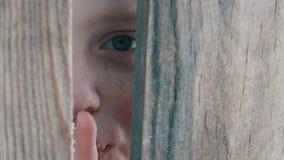 El muchacho asustado del adolescente mira a escondidas con un hueco entre una cerca o una entrada y muestra un finger de una mues almacen de metraje de vídeo