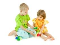 El muchacho ayuda a la muchacha a recoger un rompecabezas Imagen de archivo