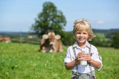 El muchacho bávaro sonriente bebe la leche en el prado con la vaca en germen Imagenes de archivo