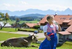 El muchacho bávaro sonriente bebe la leche en el prado con la vaca Montañas i Imagenes de archivo