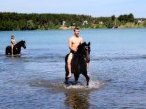El muchacho baña el caballo en el lago Foto de archivo libre de regalías