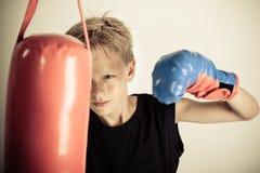 El muchacho balancea la sola mano con guantes en el saco de arena rojo Imagenes de archivo