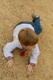 El muchacho bastante pequeño se cerró en camisa ucraniana se cae abajo en la arena Imagenes de archivo