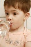 El muchacho bebe el agua de BO foto de archivo libre de regalías