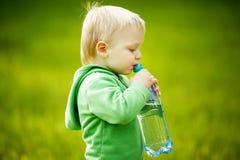 El muchacho bebe el agua mineral Imagen de archivo libre de regalías