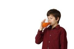 El muchacho bebe el jugo Foto de archivo libre de regalías