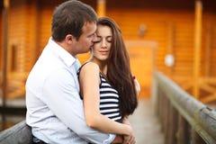 El muchacho besa una morenita blanda en el puente de madera Fotografía de archivo