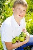 El muchacho bonito adolescente está sosteniendo manzanas verdes Fotos de archivo