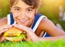 El muchacho bonito come la hamburguesa al aire libre Imagen de archivo