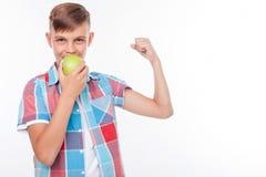 El muchacho bonito sano es fruta verde penetrante Imagen de archivo