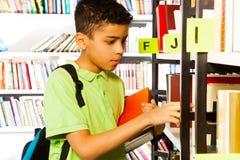 El muchacho busca los libros en el estante de la biblioteca Imágenes de archivo libres de regalías