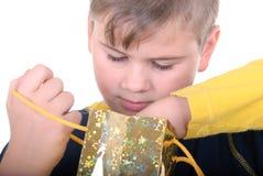 El muchacho busca para un regalo en un bolso Foto de archivo