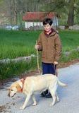 El muchacho camina con su perro en un correo Fotos de archivo libres de regalías
