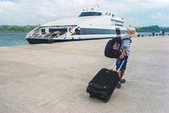 El muchacho camina en un embarcadero que lleva una maleta Fotografía de archivo