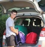 El muchacho carga el equipaje en el coche Fotos de archivo libres de regalías