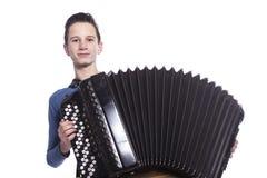 El muchacho caucásico adolescente juega el acordeón en estudio Fotografía de archivo