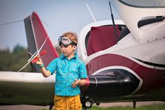 El muchacho caucásico en pantalones cortos amarillos, una camisa azul y en la aviación señala los controles el avión del juguete  imagenes de archivo