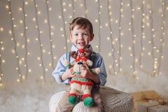 El muchacho caucásico que sostiene alces de los ciervos juega la celebración de la Navidad o del Año Nuevo Foto de archivo